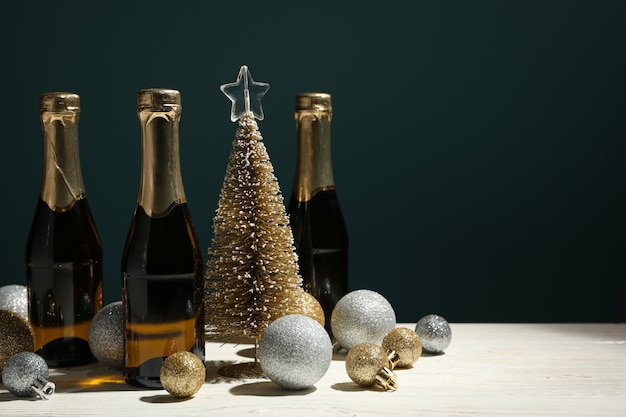 Baubles and champagne mini bottles on white wooden table, space for text