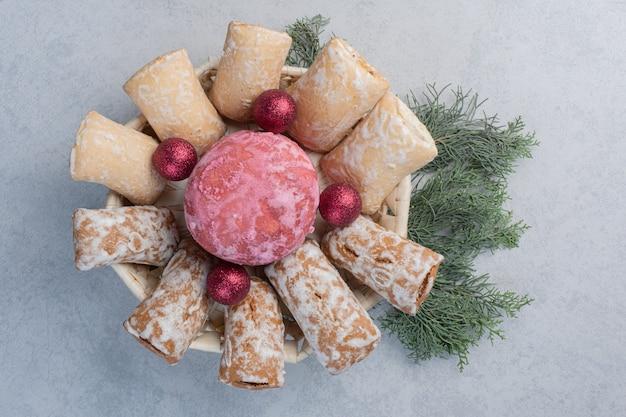 Bagattelle e biscotti impacchettati in un cestino bianco su un mucchio di rami di pino