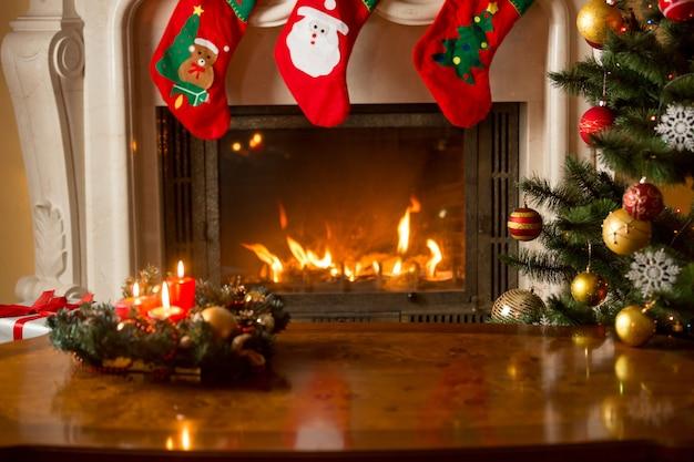 燃える暖炉の前のクリスマスツリーのつまらないもの。美しいクリスマスの背景