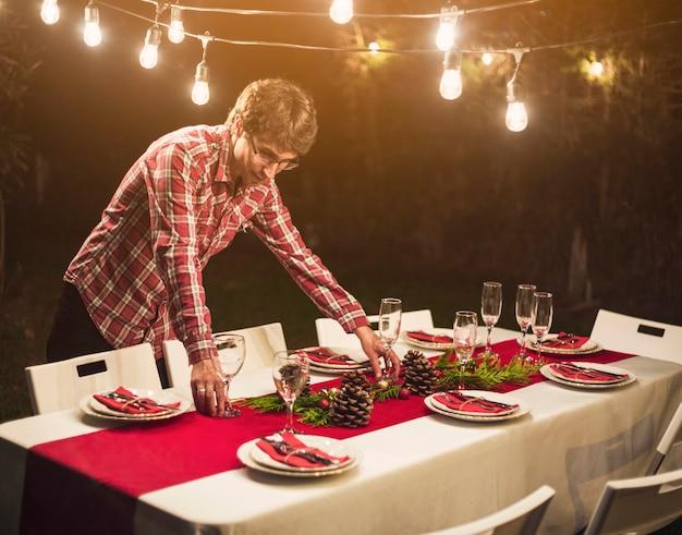 パーティーのためのbaublesとテーブルを飾る男