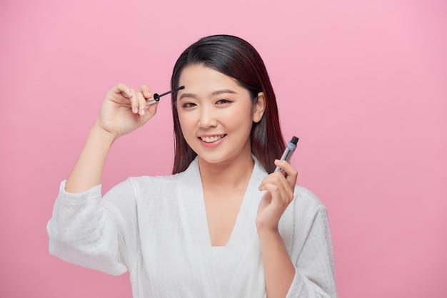 マスカラを適用する美しいアジアの女性