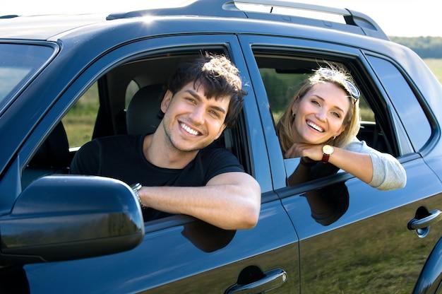 Bautiful счастливая молодая пара за рулем автомобиля