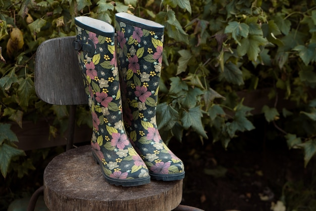 B beautiful резиновые сапоги с цветочным принтом стоят на ретро-кресле в саду
