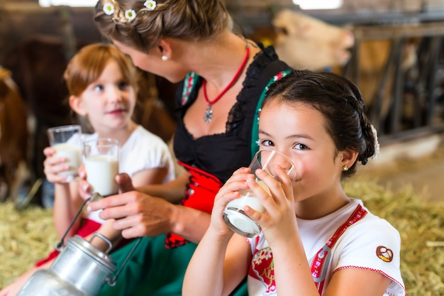 Bavaria family drinking milk in cow barn