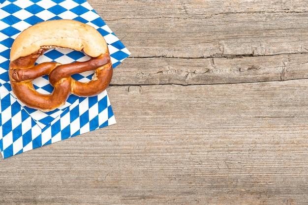 Баварский хлеб крендель деревянная доска фон