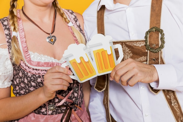 Bavarian couple holding paper beer mugs