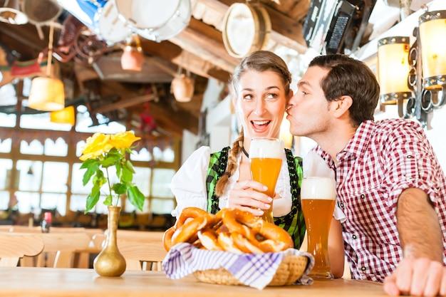 전통적인 드레스를 입고 레스토랑에서 맥주를 유혹하고 마시는 바이에른 부부