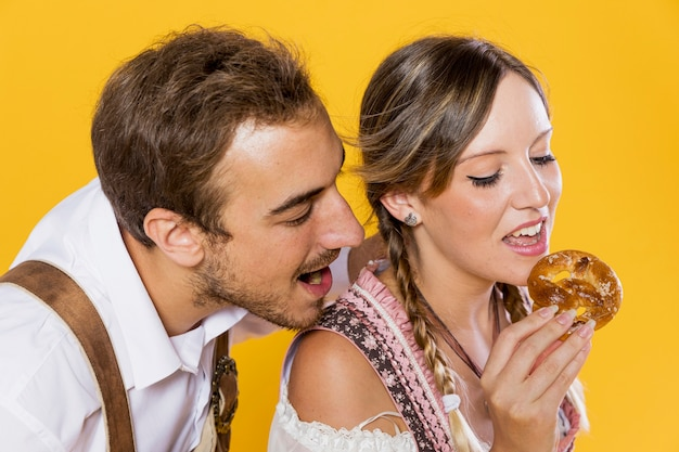 Bavarian friends eating a pretzel