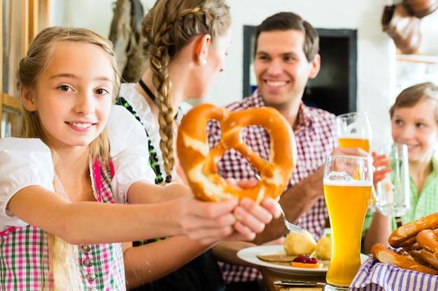 여자 옷을 입고 전통적인 레스토랑에서 가족과 함께 먹는 바이에른 소녀