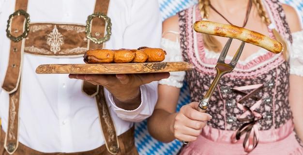 Баварский мужчина и женщина, держащая закуски октоберфест