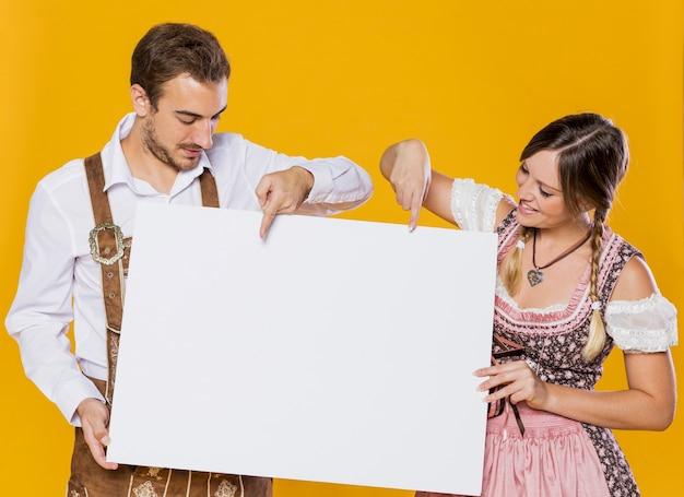 Баварский мужчина и женщина с макетом