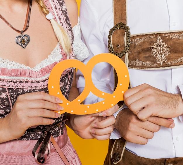 Bavarian man and woman holding pretzel