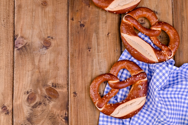 Bavarian pretzel decorated with a blue and white cloth on a rustic wooden board background and free space for text. traditional pastries for the festival