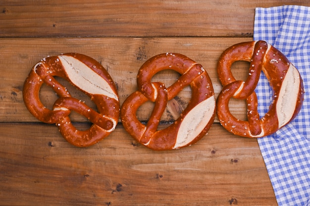 Bavarian pretzel decorated with a blue and white cloth on a rustic wooden board