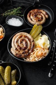 Картофельное пюре и квашеная капуста баварская колбаса, на черном столе
