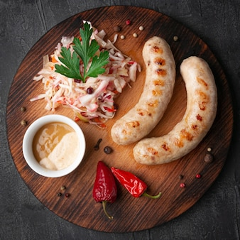 Bavarian sausages grill with pickled cabbage and mustard. garnished with parsley, cranberry and chilli. on a round wooden board. view from above. gray concrete background.