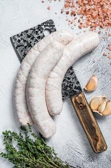 肉切り包丁に乗ったバイエルンの伝統的な白いソーセージ。白色の背景。上面図。