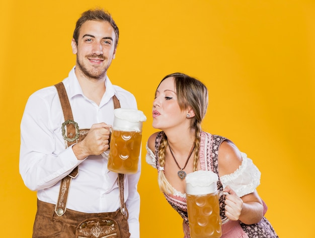 Bavarian young couple with beer mugs