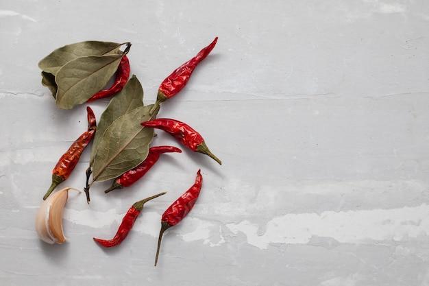 セラミックの背景に月桂樹の葉、赤唐辛子、ニンニク