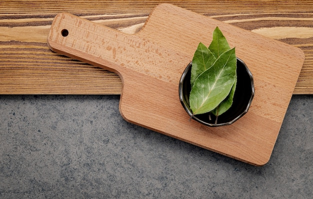 The bay leaves in ceramic bowl on shabby wooden