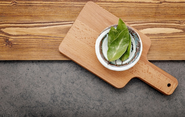 The bay leaves in ceramic bowl on shabby wooden .