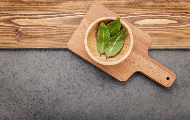 The bay leaves on cutting board set up on shabby wooden