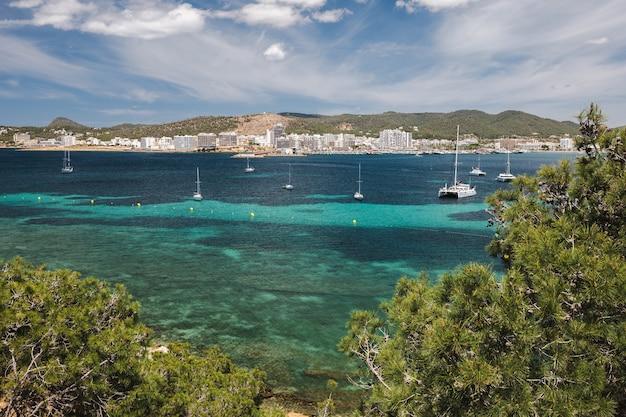 Береговая линия залива ибицы с бирюзовой водой и яхтами в солнечный летний день с видом на порт-де-сан ...