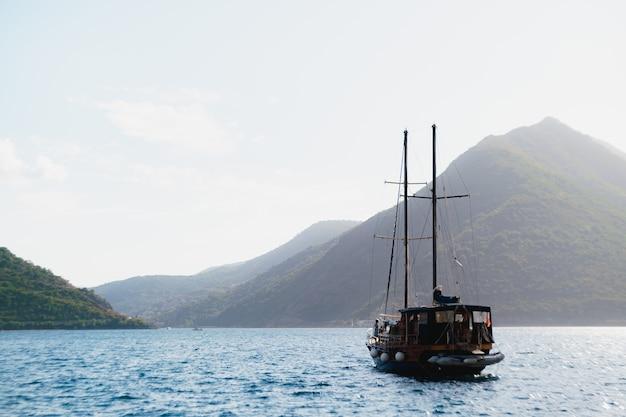山と空を背景に水に浮かぶヨットのあるコトル湾。