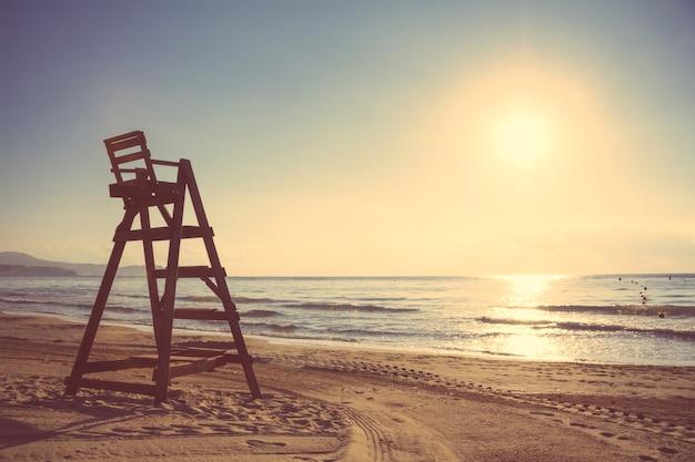 夏の日没で空の美しいビーチのベイウォッチチェア。柔らかく温かみのあるトーンエディション。
