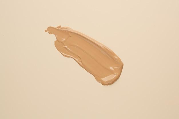 Bb, cc cream foundation tonal smudge on nude beige surface. Premium Photo