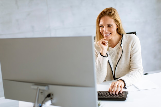 明るいモダンなオフィスでラップトップに取り組んでいる美しい実業家