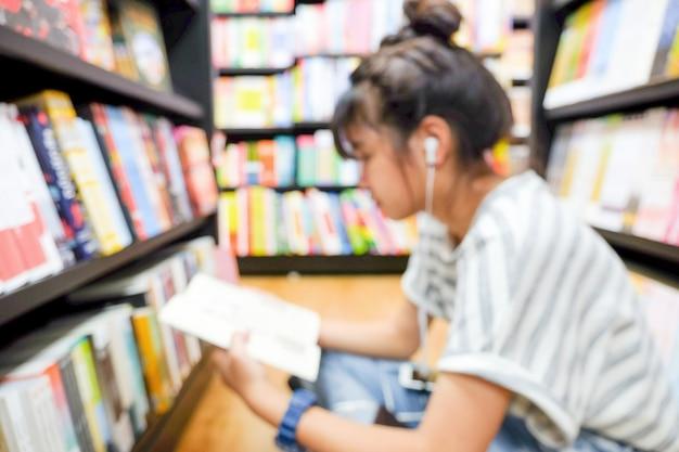 Bblur молодая девушка студент сидит и читает книгу возле книжных полок в библиотеке фон
