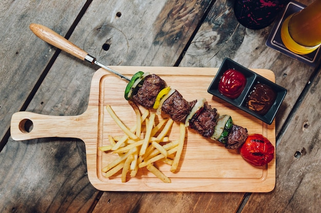 Bbq beef kebab served with french fries, tomato sauce and bbq sauce on wooden plate.