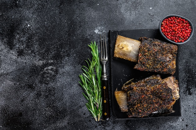Bbq beef short ribs with herbs. black background. top view. copy space.