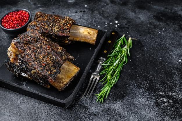 허브를 곁들인 bbq 쇠고기 갈비. 검은 배경. 평면도. 공간을 복사합니다.