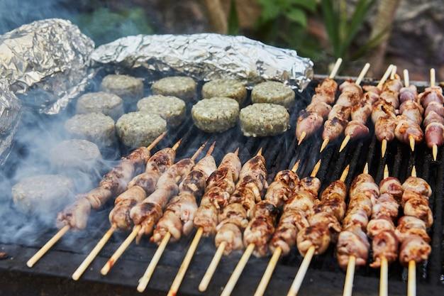 バーベキューハンバーガー、串焼きのグリルハート、スモークバーベキューパーティー。閉じる