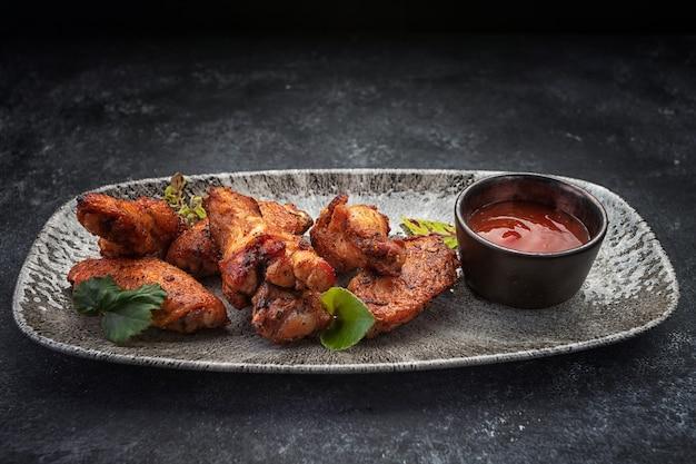 Куриные ножки bbq с соусом, на серой тарелке, на темном столе