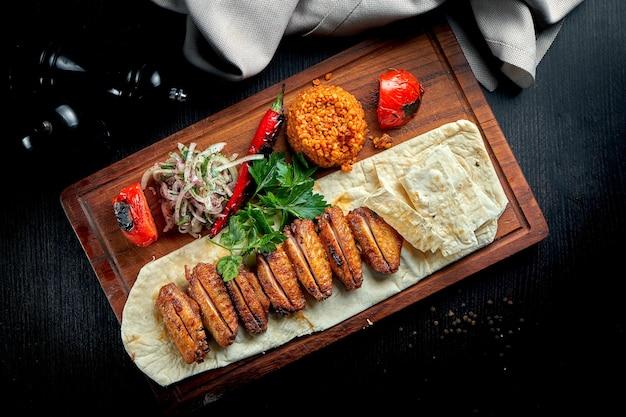 Bulgur, 구운 야채 및 절인 양파로 장식 된 bbq 닭 날개. 닭 날개 shashlik