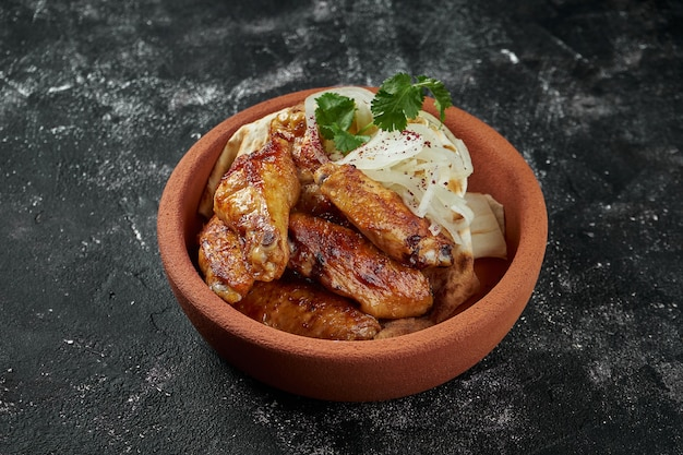 Bbq chicken wings in a spicy honey sauce with pickled onions in a ceramic bowl on a dark table. pub food. shashlik