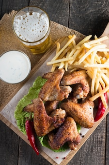 Bbq chicken wings with fries and beer.