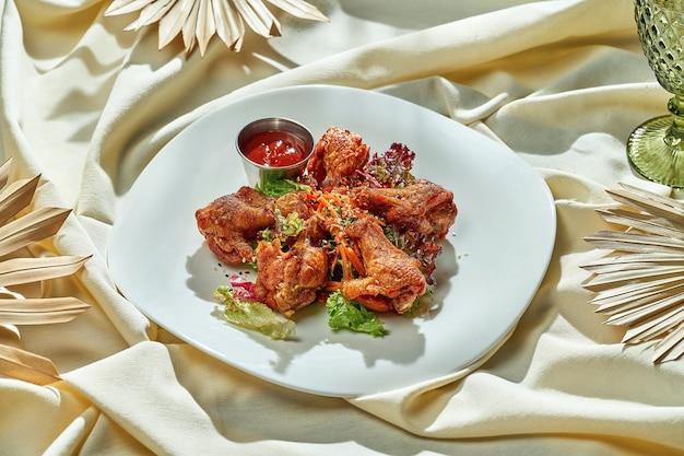 Куриные крылышки bbq с красным соусом и овощами. еда пальцами, еда в пабе