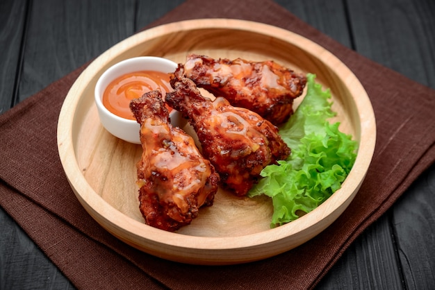Bbq chicken wings with spicy chili sauce on a wooden plate
