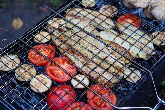 Концепция барбекю рыба в огне с грибами и помидорами крупным планом кулинария копией пространства