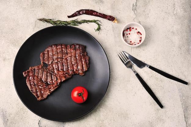 Приготовленный на гриле стейк из говядины на черной тарелке, вид сверху