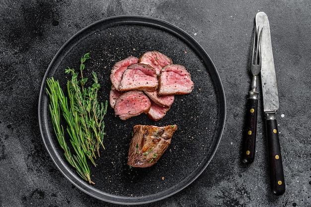 Жареный на гриле и нарезанный стейк из телячьей вырезки на тарелке
