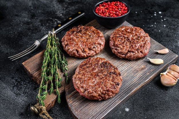 Bbq grilled beef meat patties for burger from mince meat and herbs on a wooden board