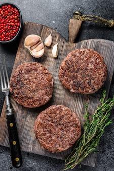 Котлеты из говядины на гриле для бургера из фарша и зелени на деревянной доске