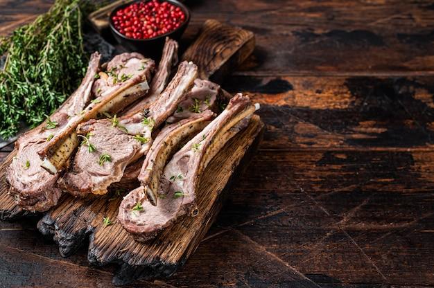 Бараньи ребрышки, приготовленные на гриле, нарезанные на мясной доске стейки с помощью ножа для мяса. темный деревянный фон. вид сверху. скопируйте пространство.