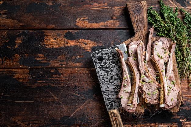 Bbq 구운 양고기 갈비 고기 식칼과 함께 정육점 보드에 스테이크를 자른다. 어두운 나무 배경입니다. 평면도. 공간을 복사합니다.