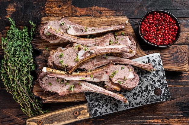 Bbq 구운 양고기 갈비 고기 칼로 정육점 보드에 스테이크를 볶습니다. 어두운 나무 배경입니다. 평면도.